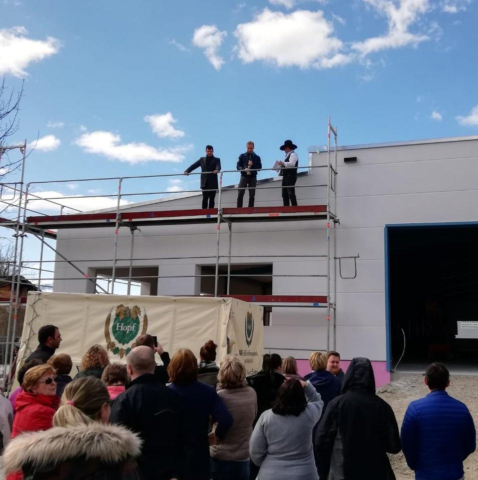 Drei Personen auf Gerüst vor Neubau und Zuschauer in unterer Bildhälfte